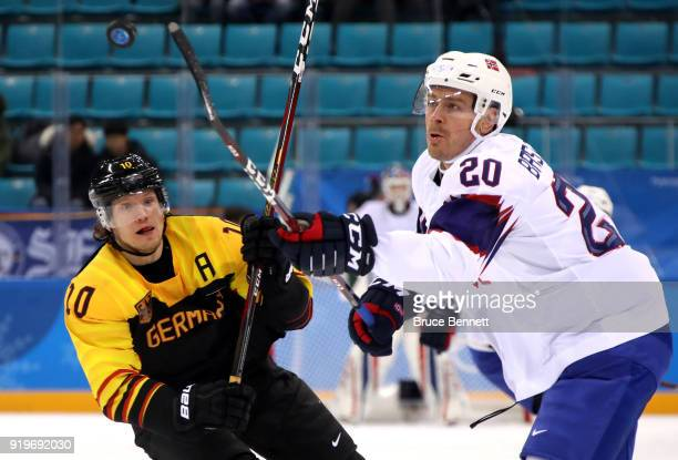 Christian Ehrhoff of Germany and Anders Bastiansen of Norway compete for a loose puck in the first period during the Men's Ice Hockey Preliminary...