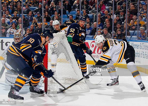 Christian Ehrhoff of the Buffalo Sabres battles for the puck alongside teammates Ryan Miller and Alexander Sulzer with Carl Soderberg of the Boston...
