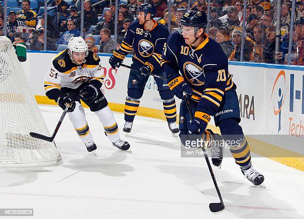 Christian Ehrhoff of the Buffalo Sabres controls the puck against Ryan Spooner of the Boston Bruins and teammate Alexander Sulzer at First Niagara...
