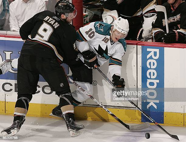 Christian Ehrhoff of the San Jose Sharks battles for the puck alongside the boards against Bobby Ryan of the Anaheim Ducks during Game Four of the...
