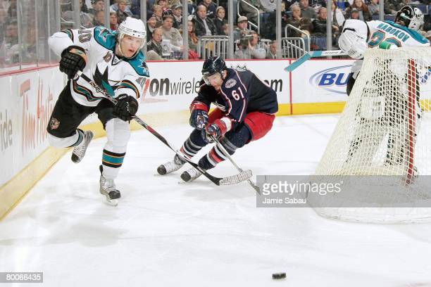Christian Ehrhoff of the San Jose Sharks passes the puck against the Columbus Blue Jackets as Rick Nash of the Blue Jackets pursues on February 27...