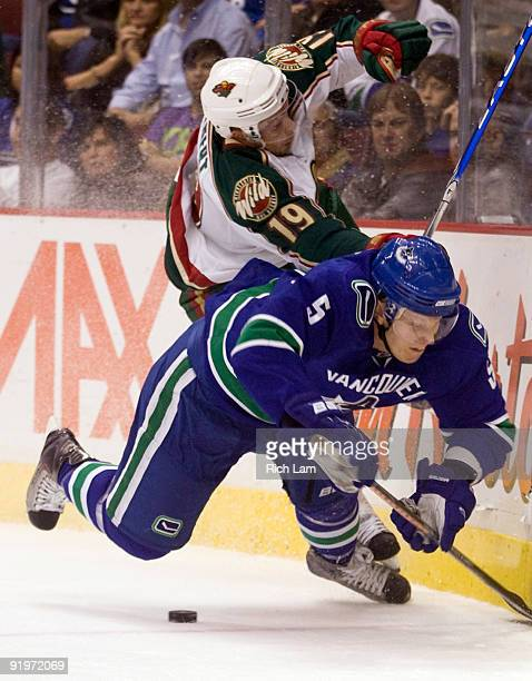 Christian Ehrhoff of the Vancouver Canucks crashes to the ice after colliding with Andy Hilbert of the Minnesota Wild during the first period of NHL...