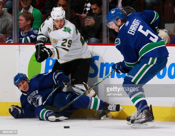 Christian Ehrhoff of the Vancouver Canucks handles the puck up ice after teammate Kyle Wellwood is checked down to the ice by Steve Ott of the Dallas...