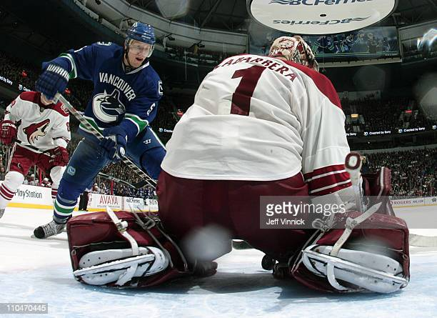 Christian Ehrhoff of the Vancouver Canucks shoots the puck between the legs of Jason LaBarbera of the Phoenix Coyotes for Vancouver's only goal...
