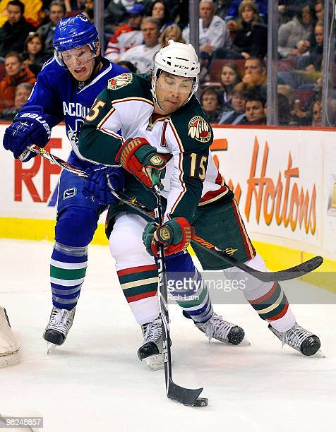 Christian Ehrhoff of the Vancouver Canucks tries to check Andrew Brunette of the Minnesota Wild during the first period of NHL action on April 04...