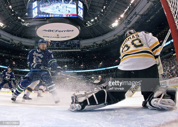 Christian Ehrhoff of the Vancouver Canucks watches Tim Thomas of the Boston Bruins make a save in Game One of the 2011 NHL Stanley Cup Finals at...