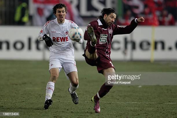 Christian Eichner of Koeln challenges Olcay Sahan of Kaiserslautern during the Bundesliga match between 1. FC Kaiserslautern and 1. FC Koeln at...