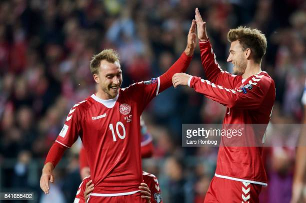 Christian Eriksen and Nicklas Bendtner of Denmark celebrate after scoring their fourth goal during the FIFA World Cup 2018 qualifier match between...