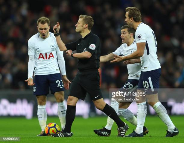 Christian Eriksen Harry Winks and Harry Kane of Tottenham Hotspur appeal to match referee Mike Jones during the Premier League match between...
