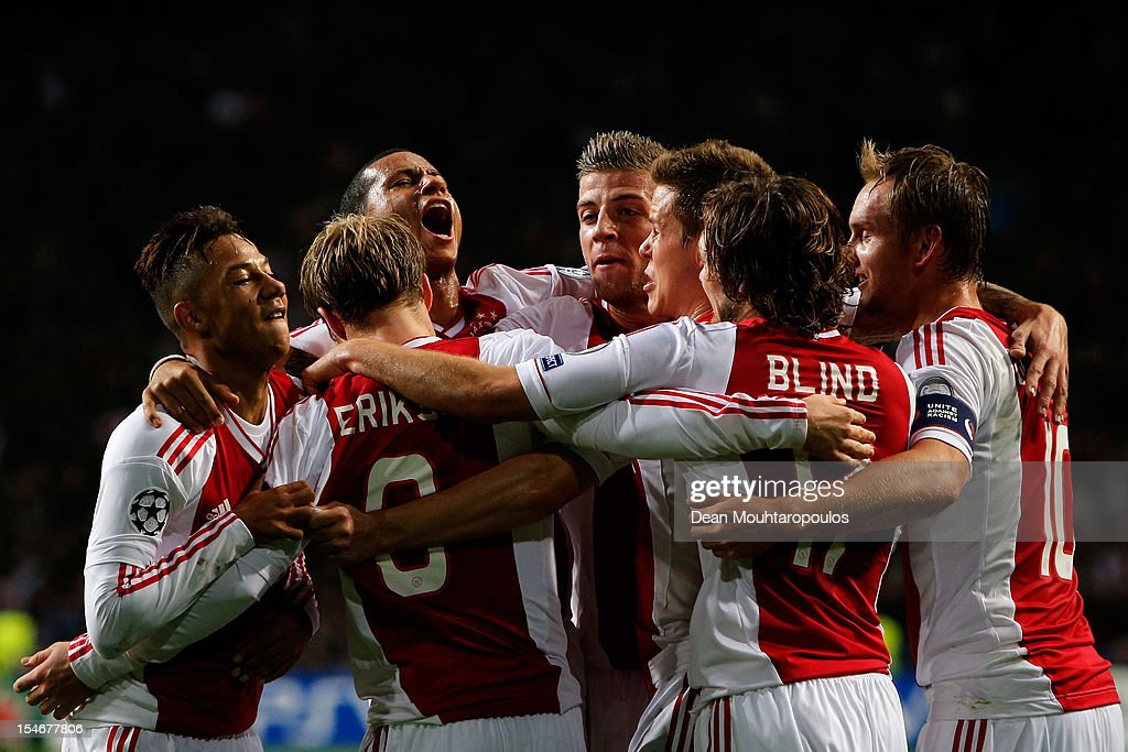 Christian Eriksen (#8) of Ajax celebrates with team mates after he shoots and scores his teams third goal of the game during the Group D UEFA Champions League match between AFC Ajax and Manchester City FC at Amsterdam ArenA on October 24, 2012 in Amsterdam, Netherlands.