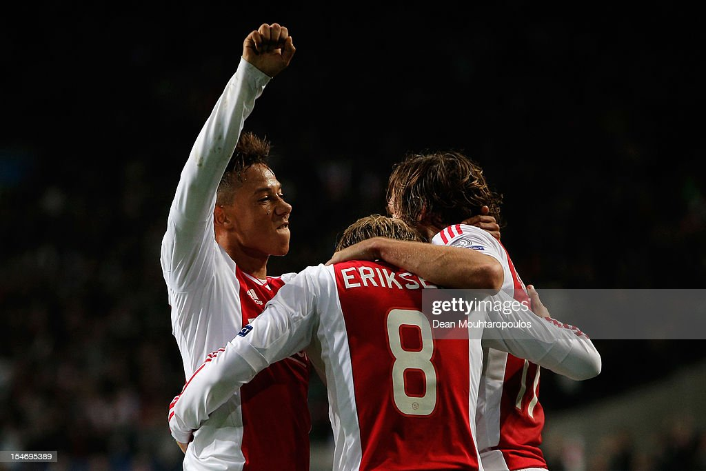 Christian Eriksen (#8) of Ajax celebrates with team mates Tobias Sana and Daley Blind after he shoots and scores his teams third goal of the game during the Group D UEFA Champions League match between AFC Ajax and Manchester City FC at Amsterdam ArenA on October 24, 2012 in Amsterdam, Netherlands.