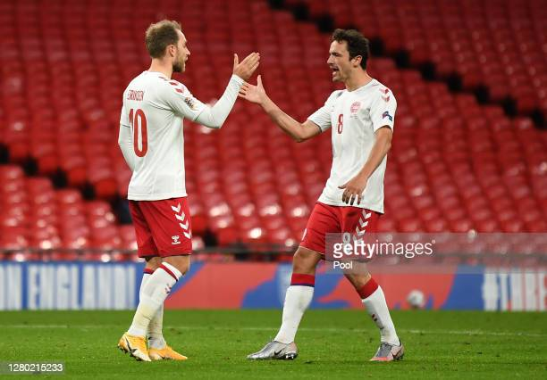 Christian Eriksen of Denmark celebrates after he scores his team's first goal from the penalty spot past Jordan Pickford of England during the UEFA...