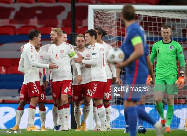 Christian Eriksen of Denmark celebrates with his team after he scores his team's first goal from the penalty spot past Jordan Pickford of England...