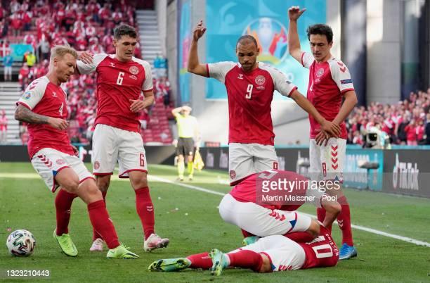 Christian Eriksen of Denmark goes down injured as team mates Simon Kjaer, Andreas Christensen, Martin Braithwaite and Thomas Delaney call for...