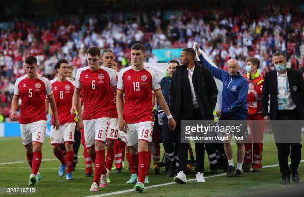 Christian Eriksen of Denmark is escorted off of the field by team mates and medics on a stretcher after receiving medical treatment during the UEFA...