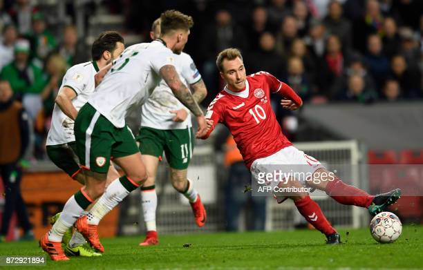 Christian Eriksen of Denmark vies for the ball against Jeff Hendrick and James McClean of Ireland during the playoff FIFA World Cup 2018...
