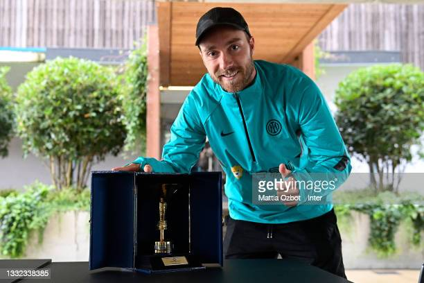 Christian Eriksen of FC Internazionale poses with his trophy from the club's Serie A title win last season at Appiano Gentile on August 04, 2021 in...