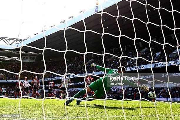 Christian Eriksen of Spurs scores the opening goal past Fraser Forster of Southampton during the Barclays Premier League match between Tottenham...