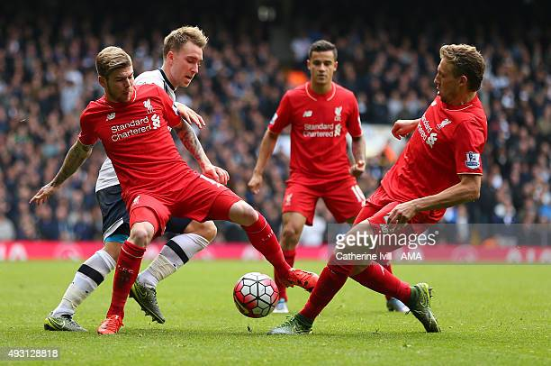 Christian Eriksen of Tottenham Hotspur battles with Alberto Moreno and Lucas Leiva of Liverpool as Philippe Coutinho looks on during the Barclays...