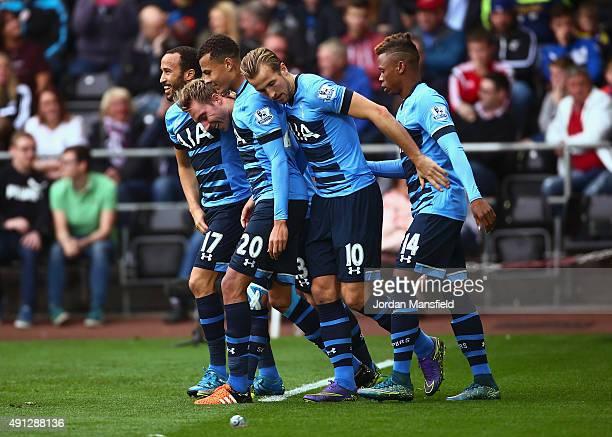 Christian Eriksen of Tottenham Hotspur celebrates scoring Tottenham's second goal with team mates during the Barclays Premier League match between...