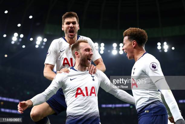Christian Eriksen of Tottenham Hotspur celebrates with teammates after scoring his team's first goal during the Premier League match between...