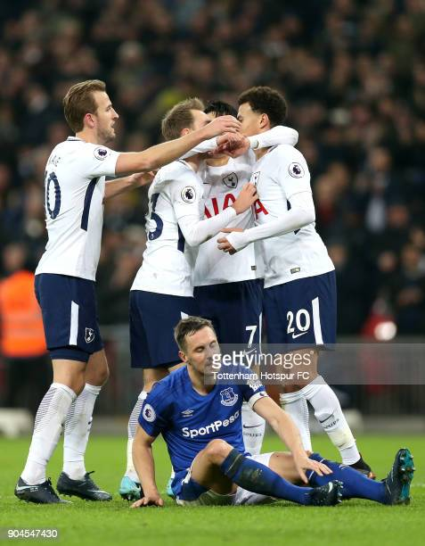 Christian Eriksen of Tottenham Hotspur celebrates with teammates after scoring his sides fourth goal as Phil Jagielka looks dejected during the...