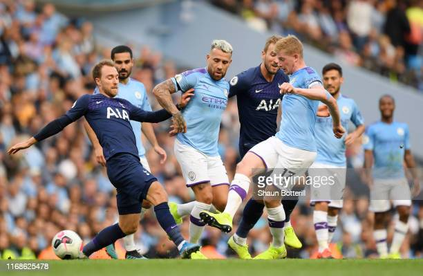 Christian Eriksen of Tottenham Hotspur challenges for the ball with Nicolas Otamendi and Kevin De Bruyne of Manchester City during the Premier League...