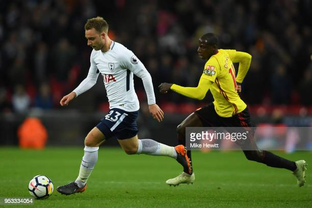 Christian Eriksen of Tottenham Hotspur is chased by Abdoulaye Doucoure of Watford during the Premier League match between Tottenham Hotspur and...