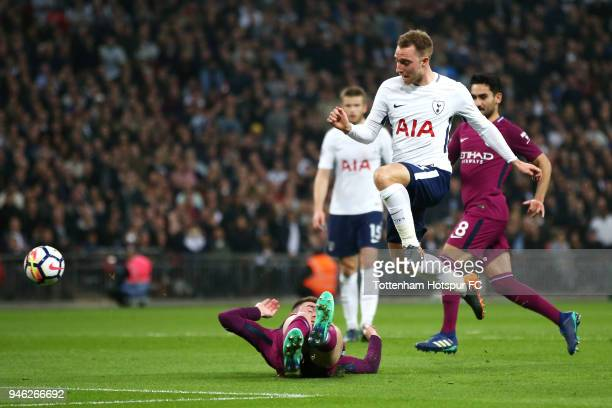 Christian Eriksen of Tottenham Hotspur scores his sides first goal past Ederson of Manchester City while under pressure from Aymeric Laporte of...