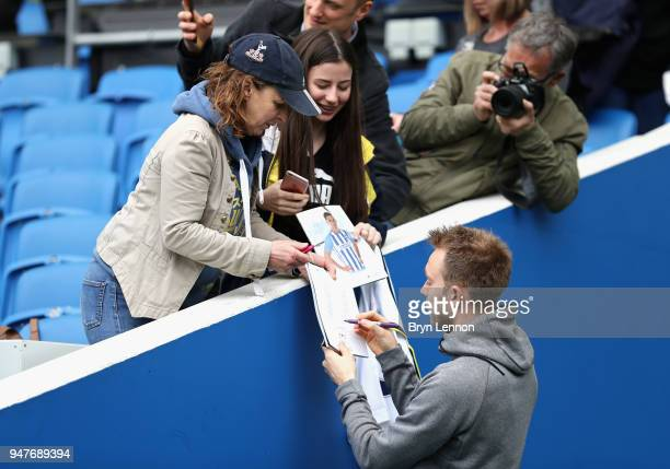 Christian Eriksen of Tottenham Hotspur signs his autograph for a fan prior to the Premier League match between Brighton and Hove Albion and Tottenham...