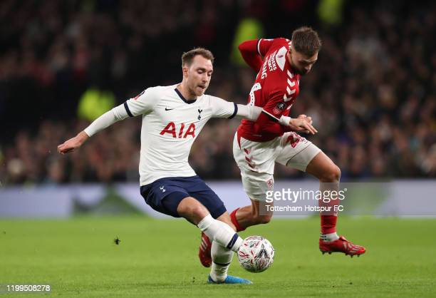 Christian Eriksen of Tottenham Hotspur tackles with Lewis Wing of Middlesbrough the FA Cup Third Round Replay match between Tottenham Hotspur and...