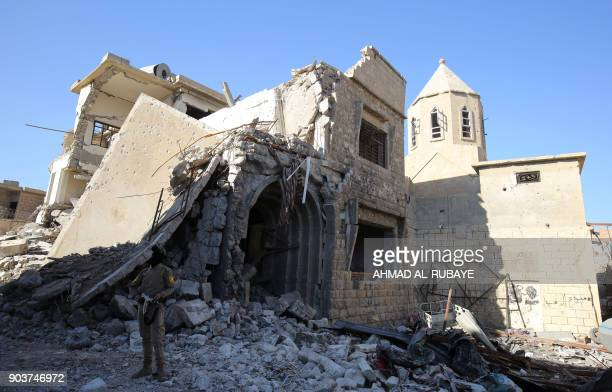 A Christian fighter from Hashed alShaabi stands near the heavily damaged Church of Saint George in the old city of Mosul on January 9 2018 Along the...