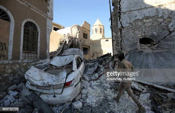 Christian fighter from Hashed alShaabi walks amidst the destruction around the Church of Saint George in the old city of Mosul on January 9 2018...