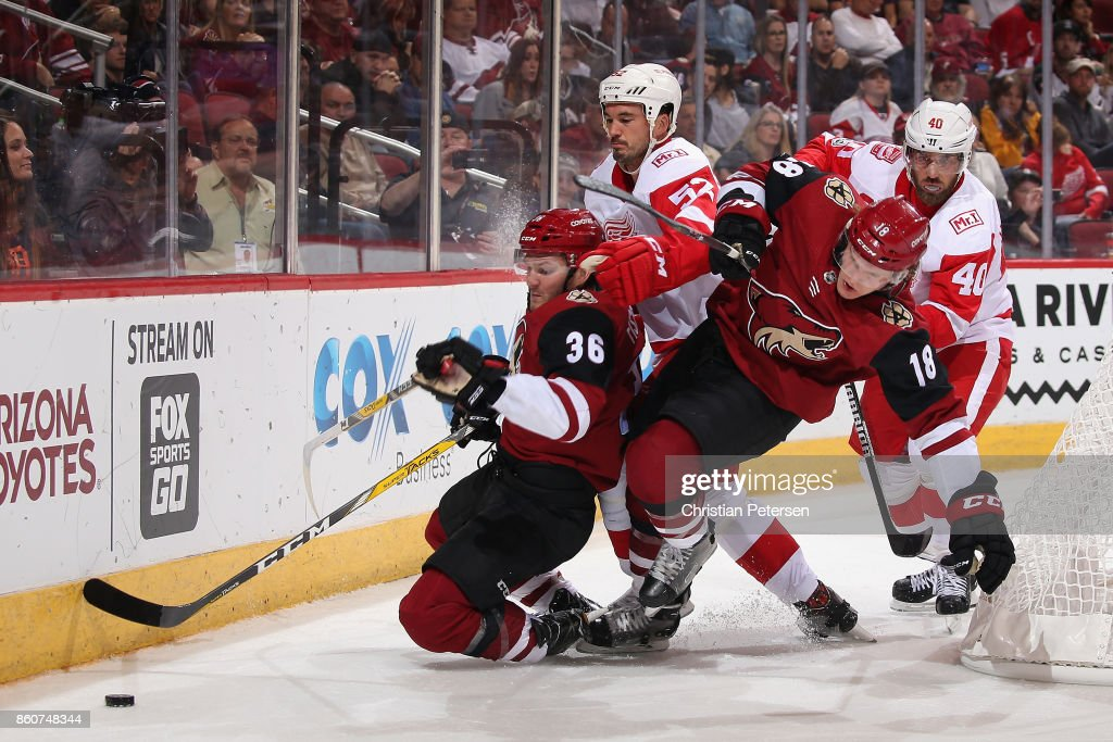 Christian Fischer #36 and Christian Dvorak #18 of the Arizona Coyotes battle for a loose puck with Jonathan Ericsson #52 and Henrik Zetterberg #40 of the Detroit Red Wings during the third period of the NHL game at Gila River Arena on October 12, 2017 in Glendale, Arizona. The Red Wings defeated the Coyotes 4-2.