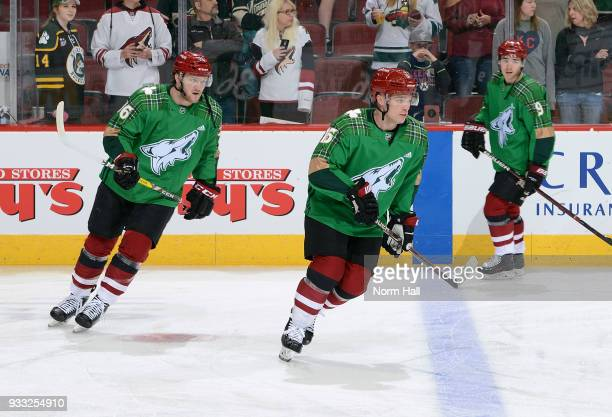 Christian Fischer and Max Domi of the Arizona Coyotes wear special green warm up jerseys in recognition of St Patrick's Day prior to a game against...
