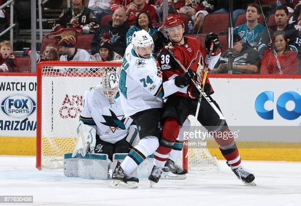 Christian Fischer of the Arizona Coyotes and Dylan DeMelo of the San Jose Sharks battle for position in front of goalie Martin Jones of the Sharks...