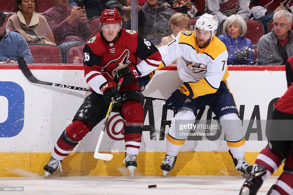 Christian Fischer #36 of the Arizona Coyotes and Yannick Weber #7 of the Nashville Predators battle for a loose puck during the second period of the NHL game at Gila River Arena on January 4, 2018 in Glendale, Arizona. The Coyotes defeated the Predators 3-2 in overtime.