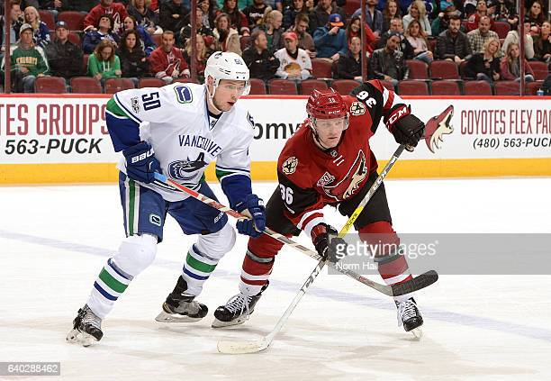 Christian Fischer of the Arizona Coyotes battles for position with Brendan Gaunce of the Vancouver Canucks during a faceoff at Gila River Arena on...
