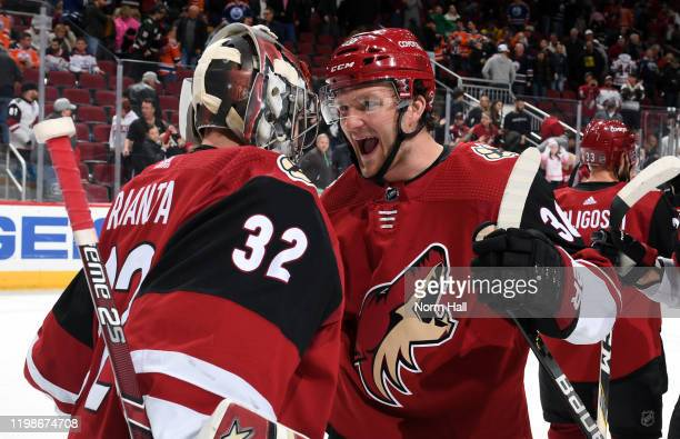 Christian Fischer of the Arizona Coyotes celebrates with goalie Antti Raanta of the Coyotes following a 3-0 shutout victory against the Edmonton...