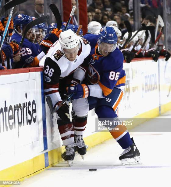 Christian Fischer of the Arizona Coyotes is hit into the boards by Nikolay Kulemin of the New York Islanders at the Barclays Center on October 24...