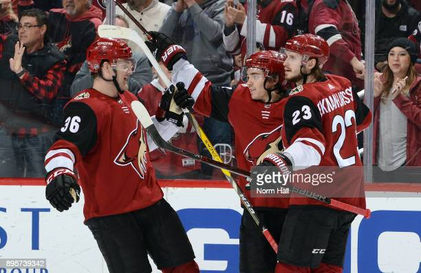 Christian Fischer of the Arizona Coyotes skates in to celebrate with teammates Clayton Keller and Oliver EkmanLarsson after his first period goal...