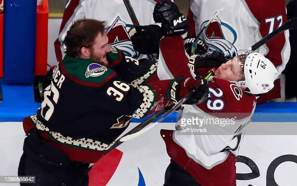 Christian Fischer of the Arizona Coyotes takes a cross checking penalty on Nathan MacKinnon of the Colorado Avalanche during the third period in Game...