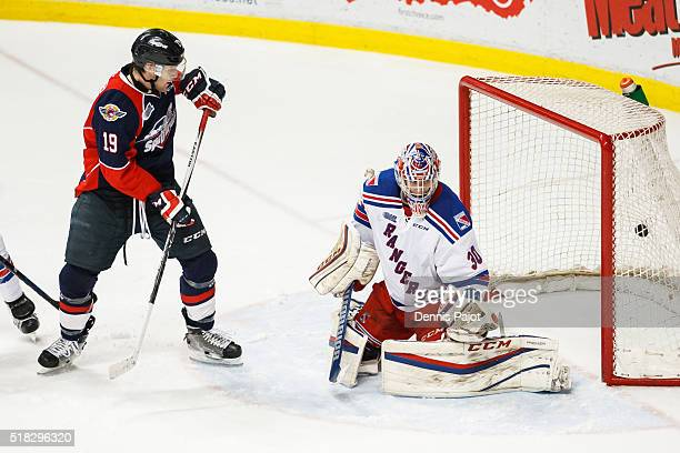 Christian Fischer of the Windsor Spitfires watches as the puck slips by goaltender Dawson Carty of the Kitchener Rangers during game 4 of the Western...