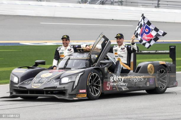 Christian Fittipaldi L of Brazil and Joao Barbosa R of Portugalride with teammate Felipe Albuquerque of Portugal to victory lane after winning the...