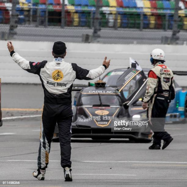 Christian Fittipaldi of Brazil greets teammate Felipe Albuquerque of Portugal on pit road after winning the Rolex 24 at Daytona IMSA WeatherTech...