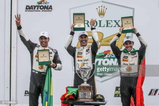 Christian Fittipaldi of Brazil Joao Barbosa of Portugal and Felipe Albuquerque of Portugal celebrate with Rolex watches in victory lane after winning...
