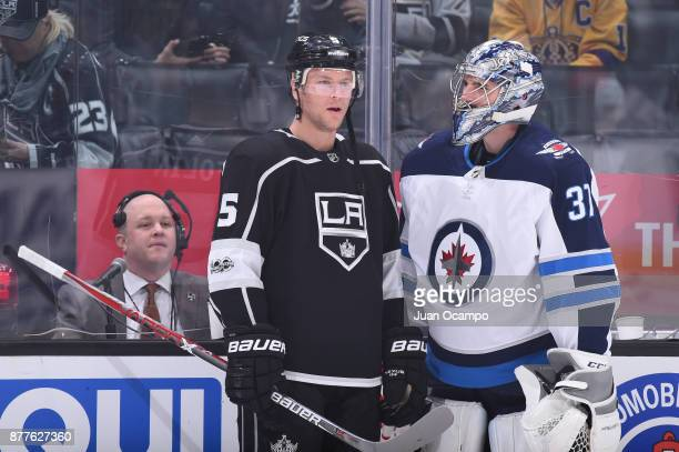 Christian Folin of the Los Angeles Kings and Connor Hellebuyck of the Winnipeg Jets converse before a game at STAPLES Center on November 22 2017 in...