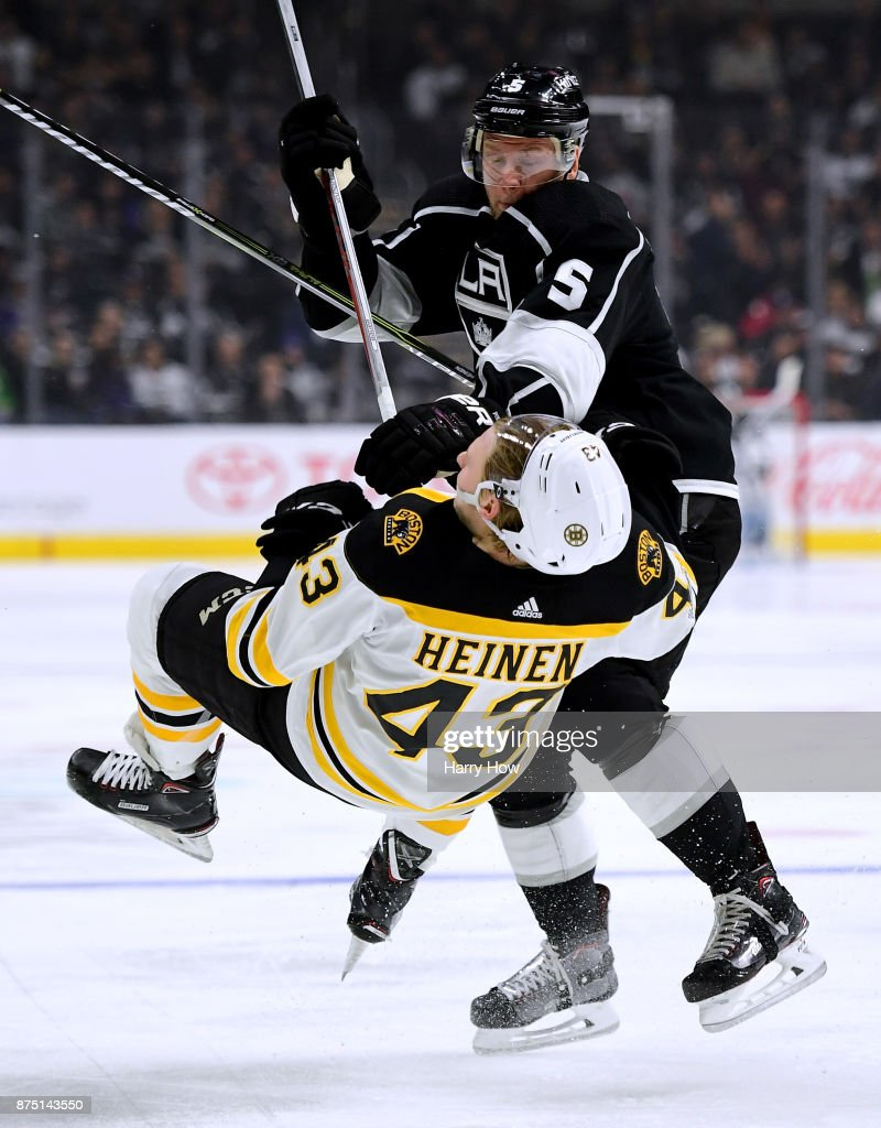 Christian Folin #5 of the Los Angeles Kings checks Danton Heinen #43 of the Boston Bruins during the second period at Staples Center on November 16, 2017 in Los Angeles, California.
