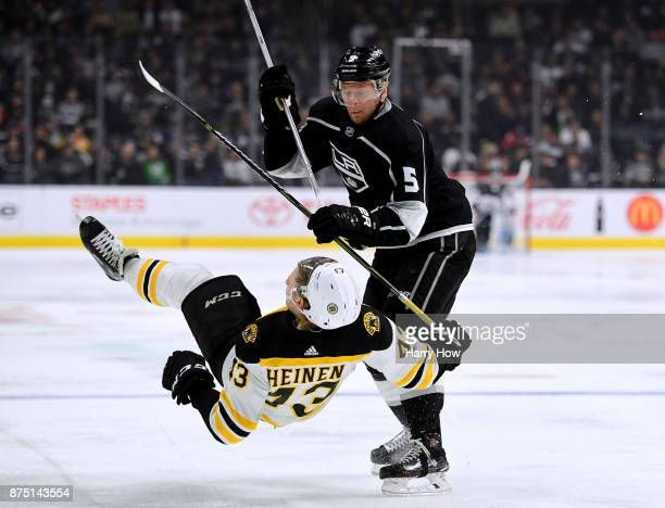 Christian Folin of the Los Angeles Kings checks Danton Heinen of the Boston Bruins during the second period at Staples Center on November 16 2017 in...