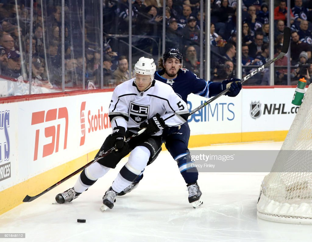 Christian Folin #5 of the Los Angeles Kings plays the puck away from Nic Petan #19 of the Winnipeg Jets during second period action at the Bell MTS Place on February 20, 2018 in Winnipeg, Manitoba, Canada.